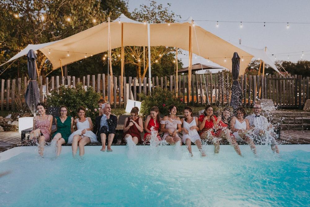 Mariés et invités, les pieds dans l'eau, s'éclaboussant, au domaine de Baulieu à Auch dans le Gers